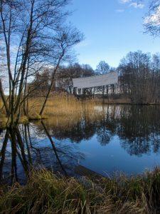 Ein Bild von dem Fluss Havel, umgeben von Bäumen, die sich im Wasser spiegeln. Über dem Fluss, zwischen zwei Bäumen hängt ein Banner, von dem nur die Rückseite zu sehen ist.