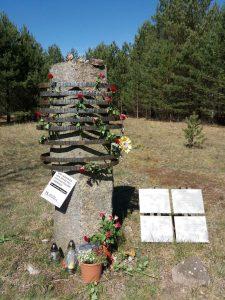Der Gedenkstein mit Blumen und Kerzen auf dem Gedenkort. Auf dem Stein steht.