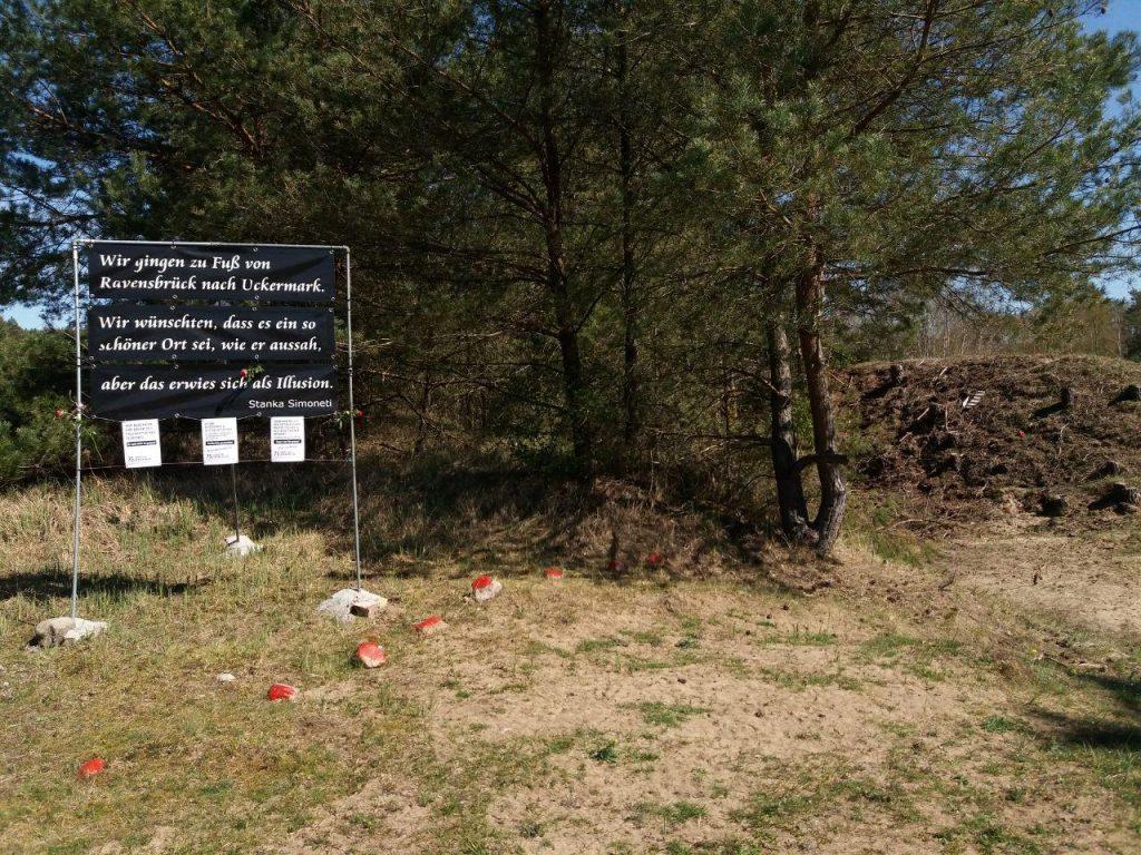 """Ein Blick auf das ehemalige Lagertor auf dem Gelände des KZ Uckermark. Links steht ein Schild mit dem Zitat einer Überlebenden: """"Wir gingen zu Fuß von Ravensbrück nach Uckermark. Wir wünschten, dass es ein so schöner Ort sei, wie er aussah, aber das erwies sich als Illusion."""" Stanka Simoneti. Davor liegen ein paar rot markierte Steine, dahinter sind Bäume."""