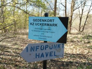 """Zu sehen ist ein Wegweiser mit der Aufschrift """"Gedenkort KZ Uckermark"""" Darunter ist ein weiterer Wegweiser mit der Aufschrift """"Infopunkt Havel"""""""